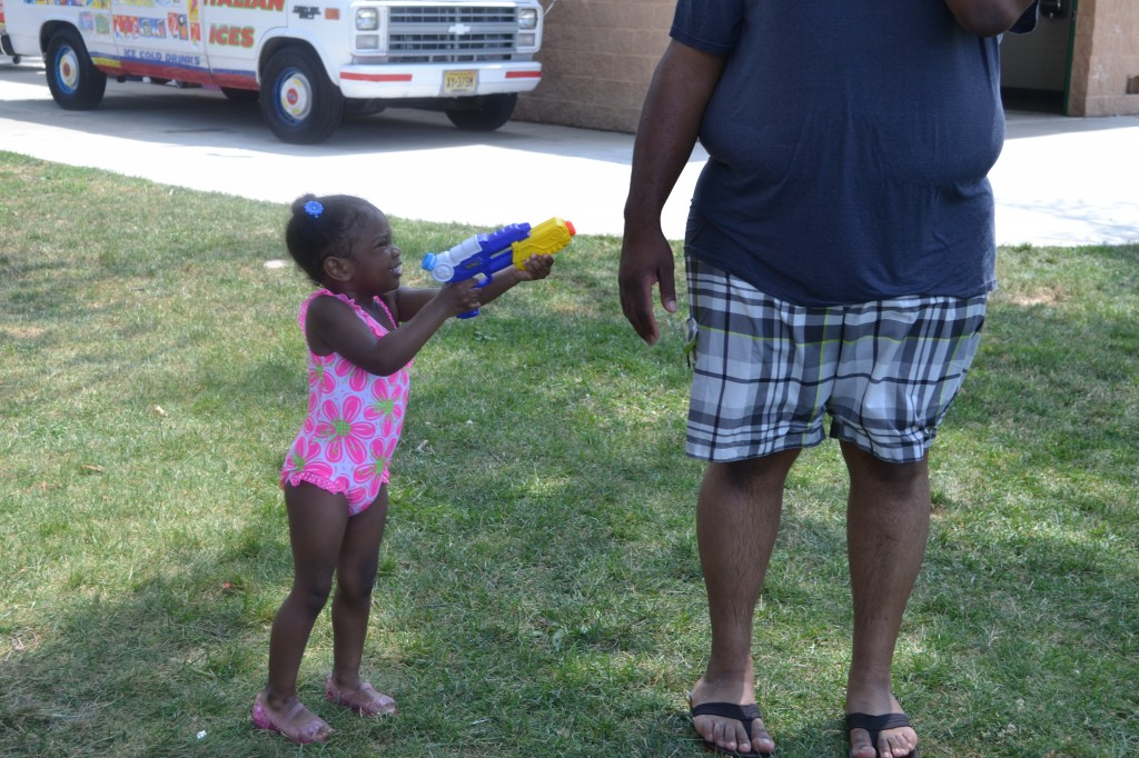 little girl shooting daddy with her water gun