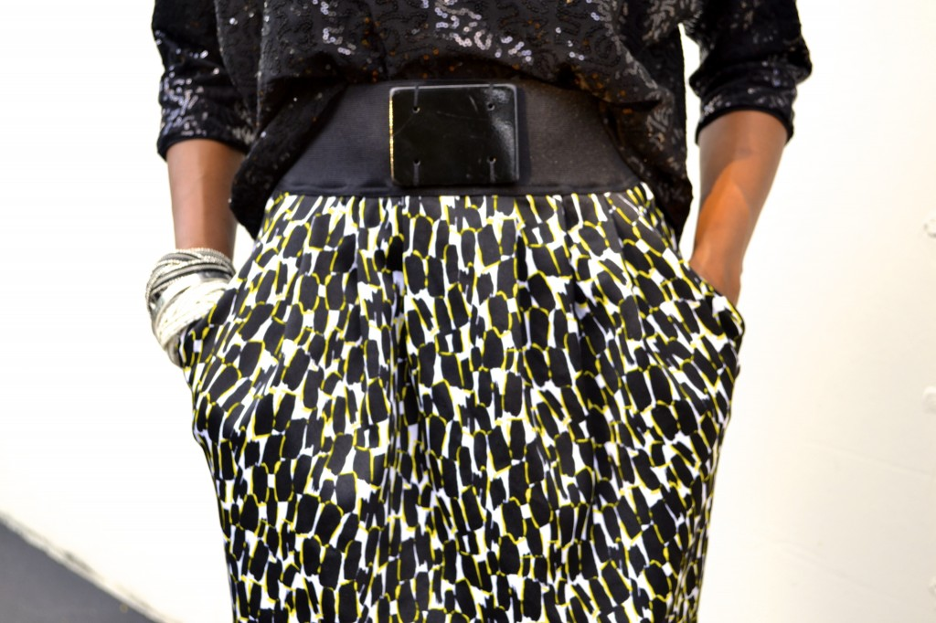 black sequin shirt, black, white and yellow skirt and arm candy