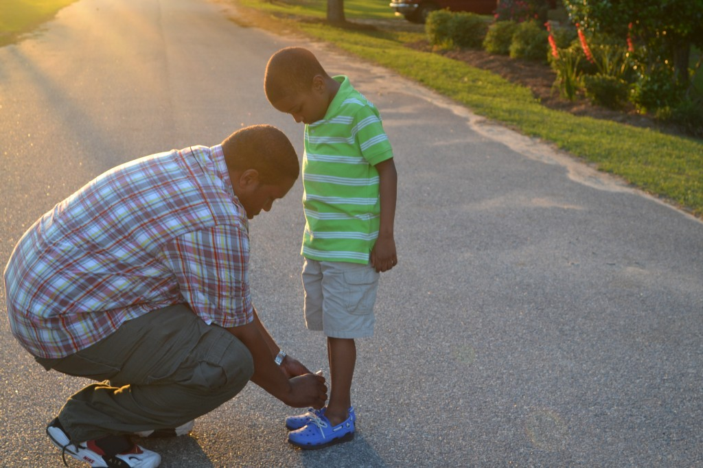 Dad tying son's shoes