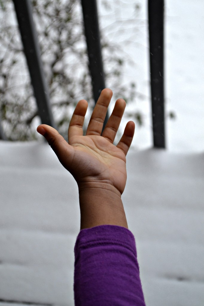 Little kid hand catching snow