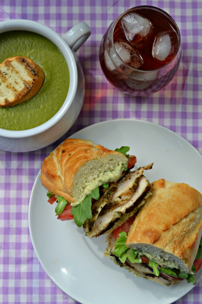 Delicious grilled pesto chicken sandwich paired with pea pesto soup and a glass of iced tea. Perfect for summer and fall meal plans!