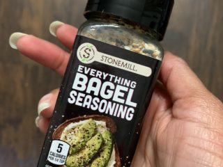 a hand holding a bottle of everything bagel seasoning