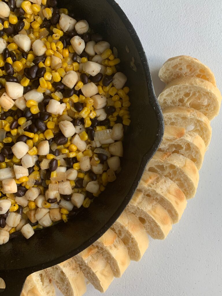 scallop and corn succotash in a cast iron skillet with sliced french baguette on the side.